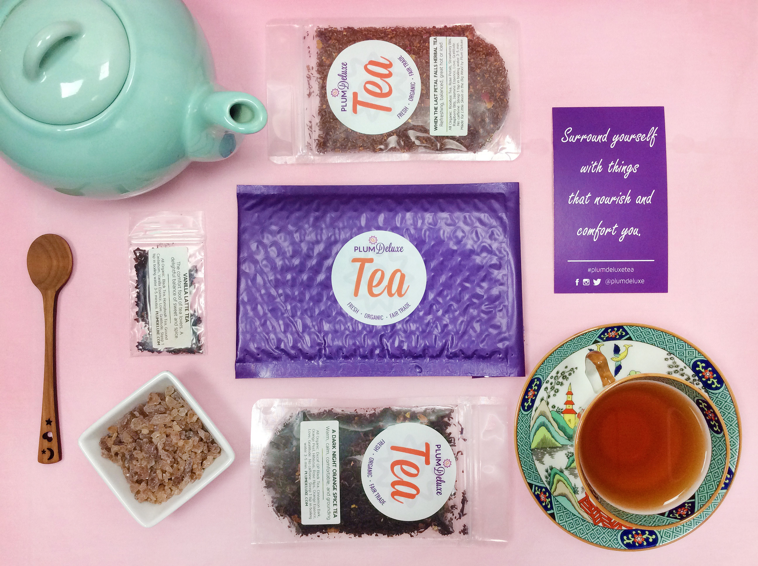 Overhead view of a tea of the month club shipment, including purple package, encouragement card, two packages of Plum Deluxe loose leaf tea, a dish of rock sugar, cherrywood spoon, light blue teapot, and teacup arranged on a pink tablecloth.
