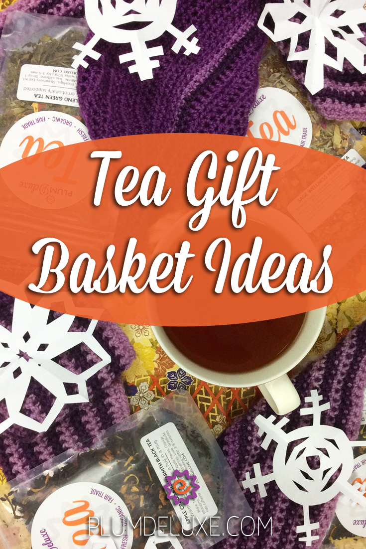 Overhead view of a mug of tea, purple crochet scarf, bags of Plum Deluxe loose leaf tea, and paper snowflakes arranged on floral wrapping paper. The overlay text reads: tea gift basket ideas.