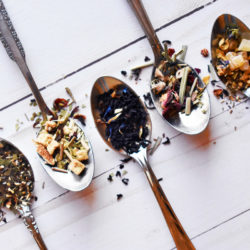 Overhead view of five silver teaspoons full of different types of tea arranged in a line on a light wood table.