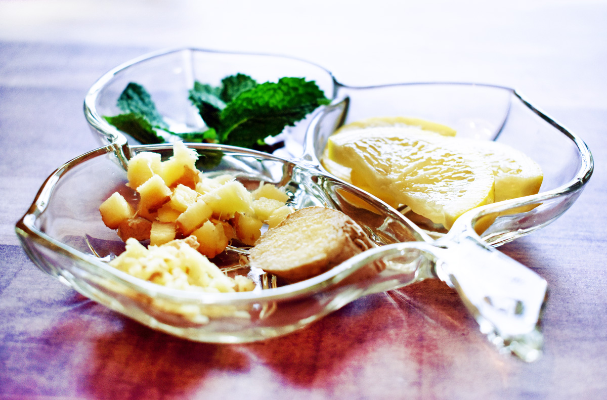 A clover-shaped dish holds sprigs of mint, slices of lemon, and slices of ginger root.
