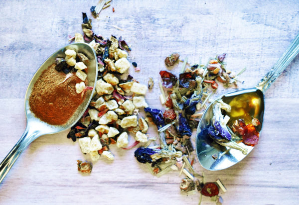 Overhead view of two teaspoons. The one on the left holds powdered cinnamon, while the one on the right holds honey and herbs. They are surrounded by dried hibiscus, fruit pieces, rosehips, and flowers and are sitting on a white-washed table.