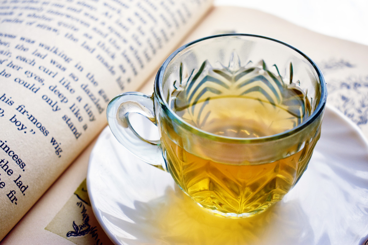 A clear cut glass teacup filled with light-colored tea sits on a white saucer on top of an open book.