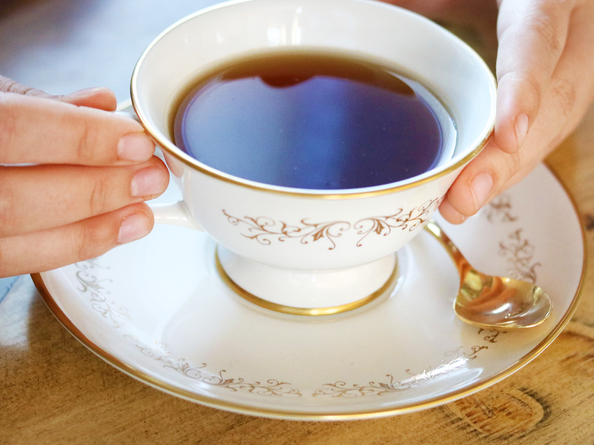 Two hands hold a white and gold teacup full of tea over a wooden table. A gold spoon rests on the saucer.