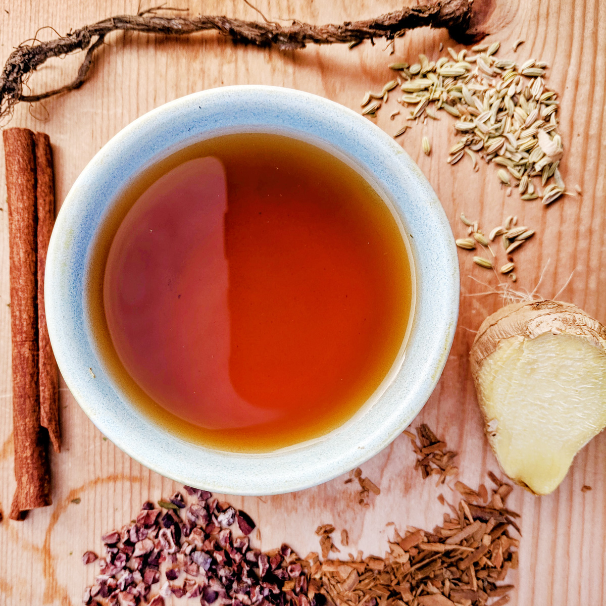 Overhead view of a cup of tea surrounded by various spices and roots such as cinnamon, ginger, and fennel on a wooden table.
