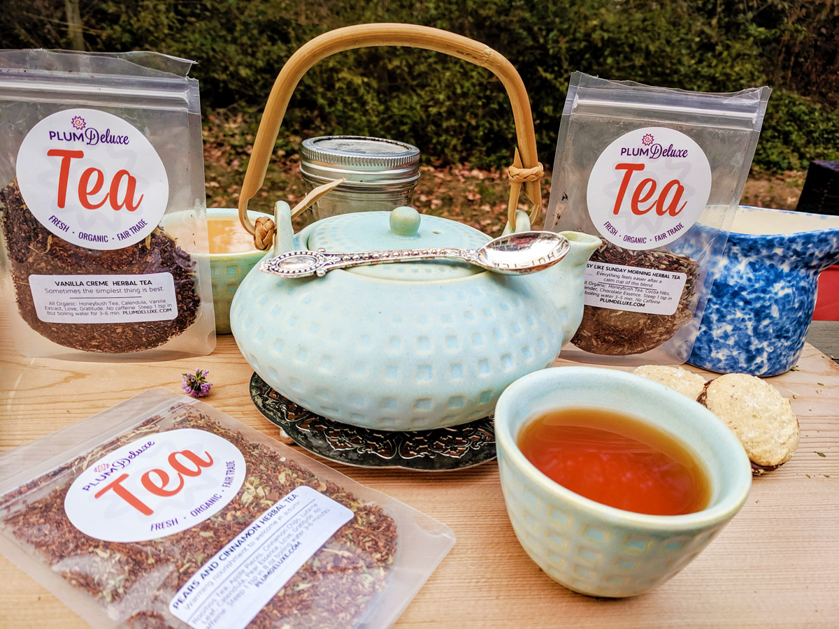 A light blue teapot with bamboo handle sits on a wooden table surrounded by matching teacups, cookies, and three bags of Plum Deluxe caffeine free herbal tea.