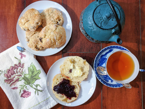 Overhead view of a plate of raisin scones in the upper left corner of a wooden table. Clockwise are a blue cast iron tea pot, a blue and white teacup and saucer full of tea, a plate holding a sliced raisin scone slathered in butter and jam, and a white and floral print tea towel.