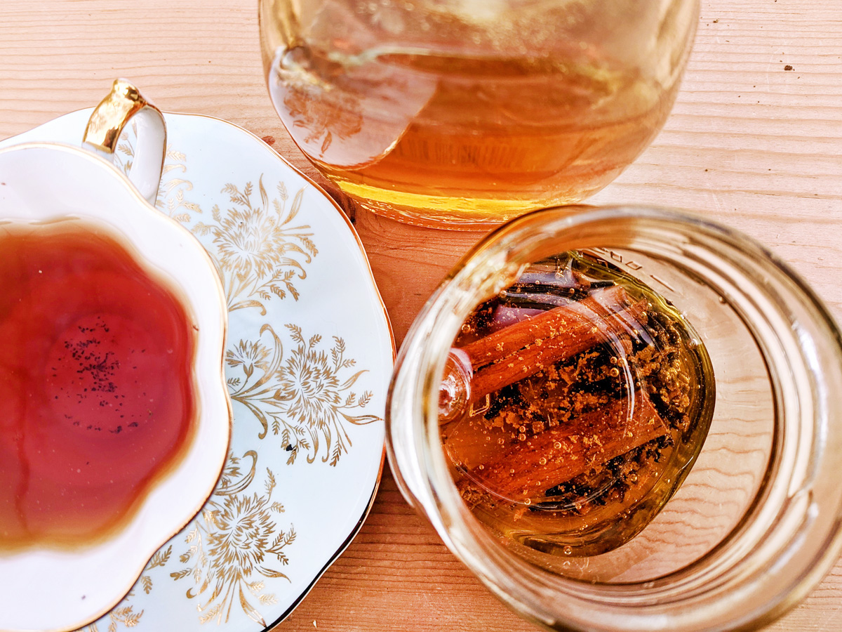 Overhead view of a white teacup and saucer with a gold leaf pattern, a jar of plain honey, and a jar of honey and cinnamon sticks arranged on a wooden table.