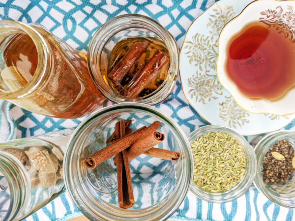 Overhead view of a white teacup and saucer full of tea and five mason jars of various sizes and shapes, all holding things like honey, cinnamon sticks, fennel, and other herbs and spices.