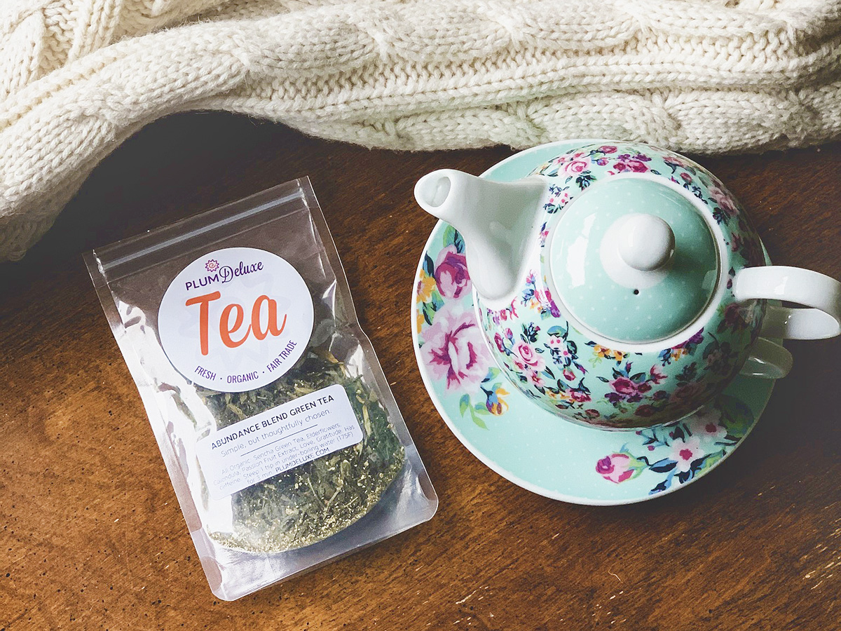 Overhead view of a blue teapot with a pink and blue floral design next to a bag of Plum Deluxe green tea on a wooden table. A white cable knit blanket is arranged next to them.
