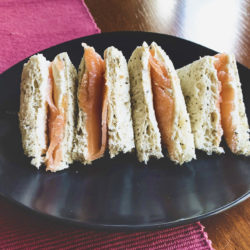 Four smoked salmon tea sandwiches are arranged in a row on a black plate.
