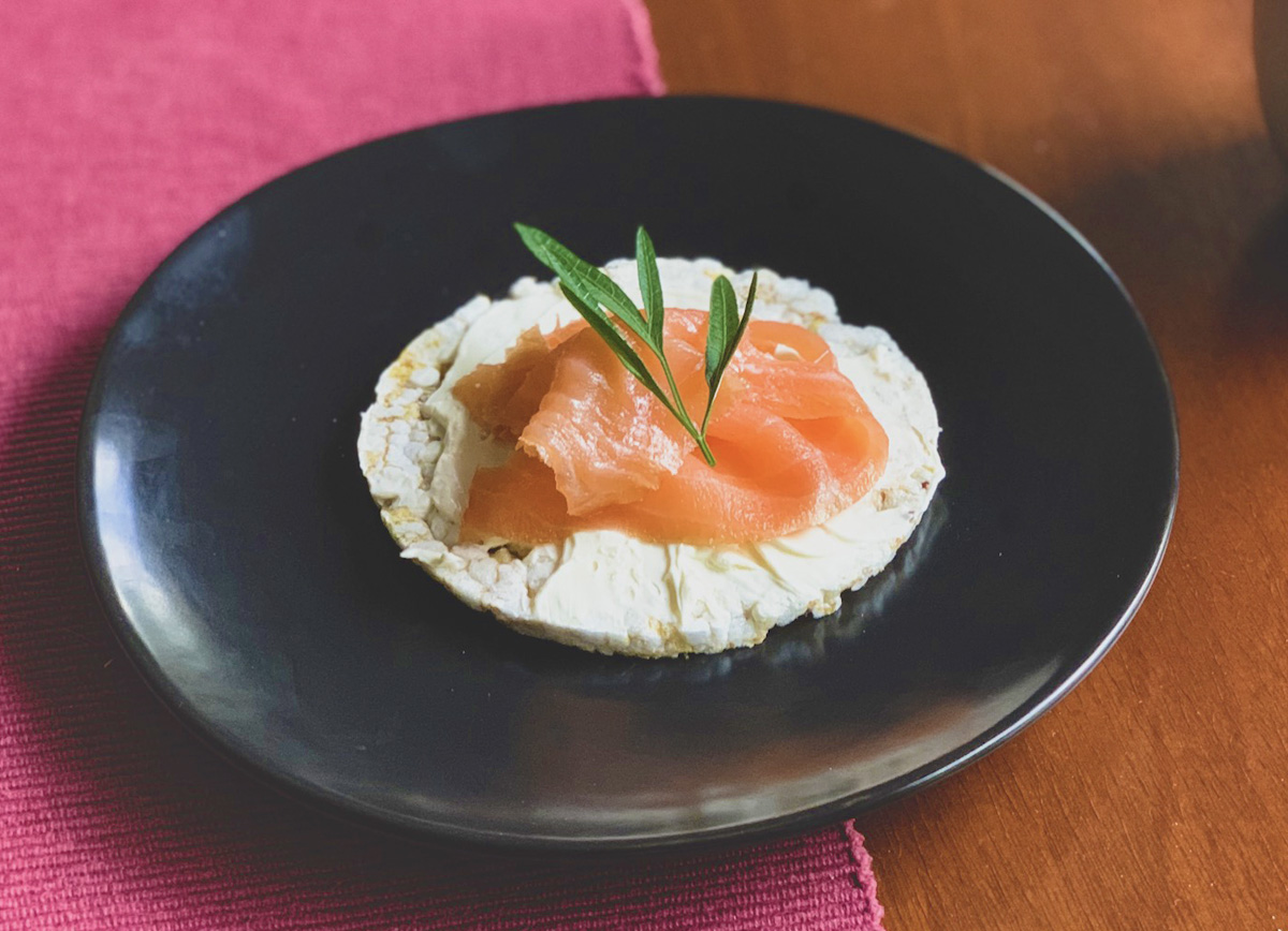 Smoked salmon and cream cheese are layered on a rice cake, which sits in the middle of a black plate.