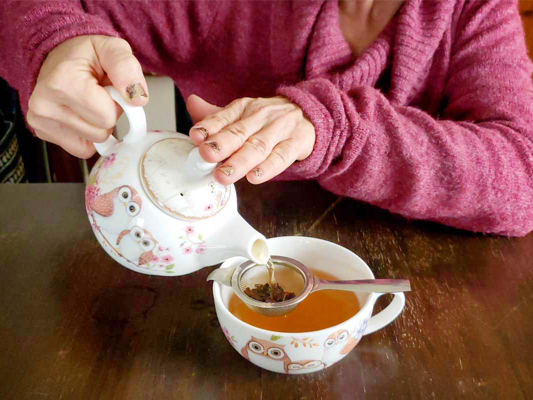 A person in a rose colored sweater pours tea from a teapot with owls on it. The tea is poured through a metal tea strainer and into a matching teacup with owls.