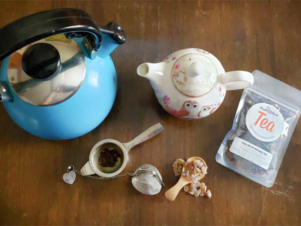 Overhead view of things for making tea, including a blue tea kettle, a teapot with owls on it, a bag of loose leaf tea, a metal tea strainer, a mesh tea ball, and a wooden scoop of rock sugar.