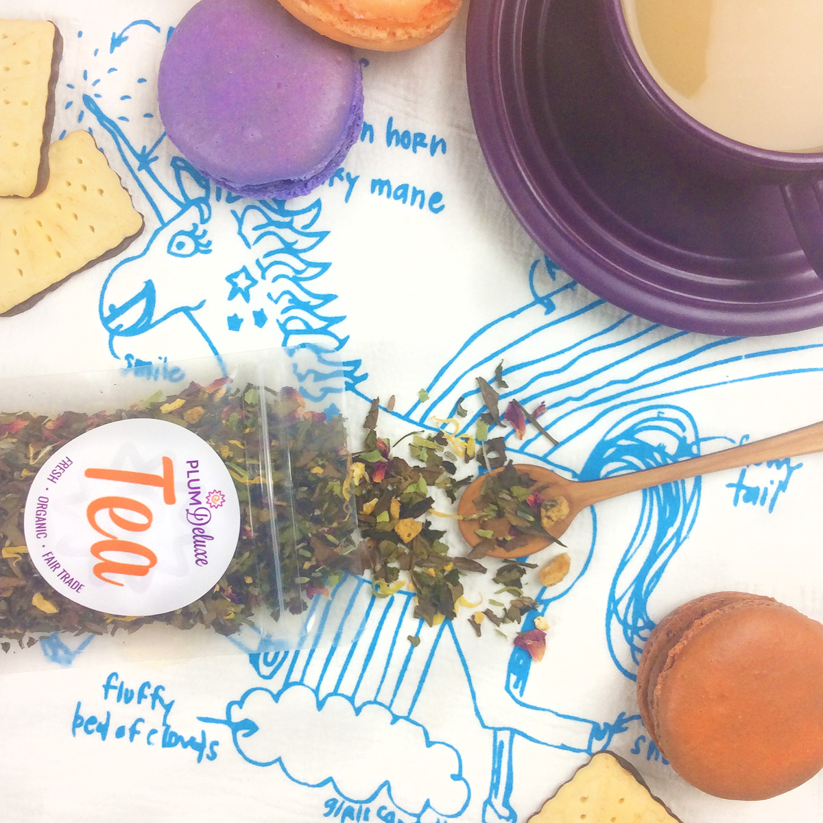 Overhead view of an open bag of Plum Deluxe loose leaf tea, cherrywood spoon, purple teacup and saucer, and macarons on a unicorn print tea towel.