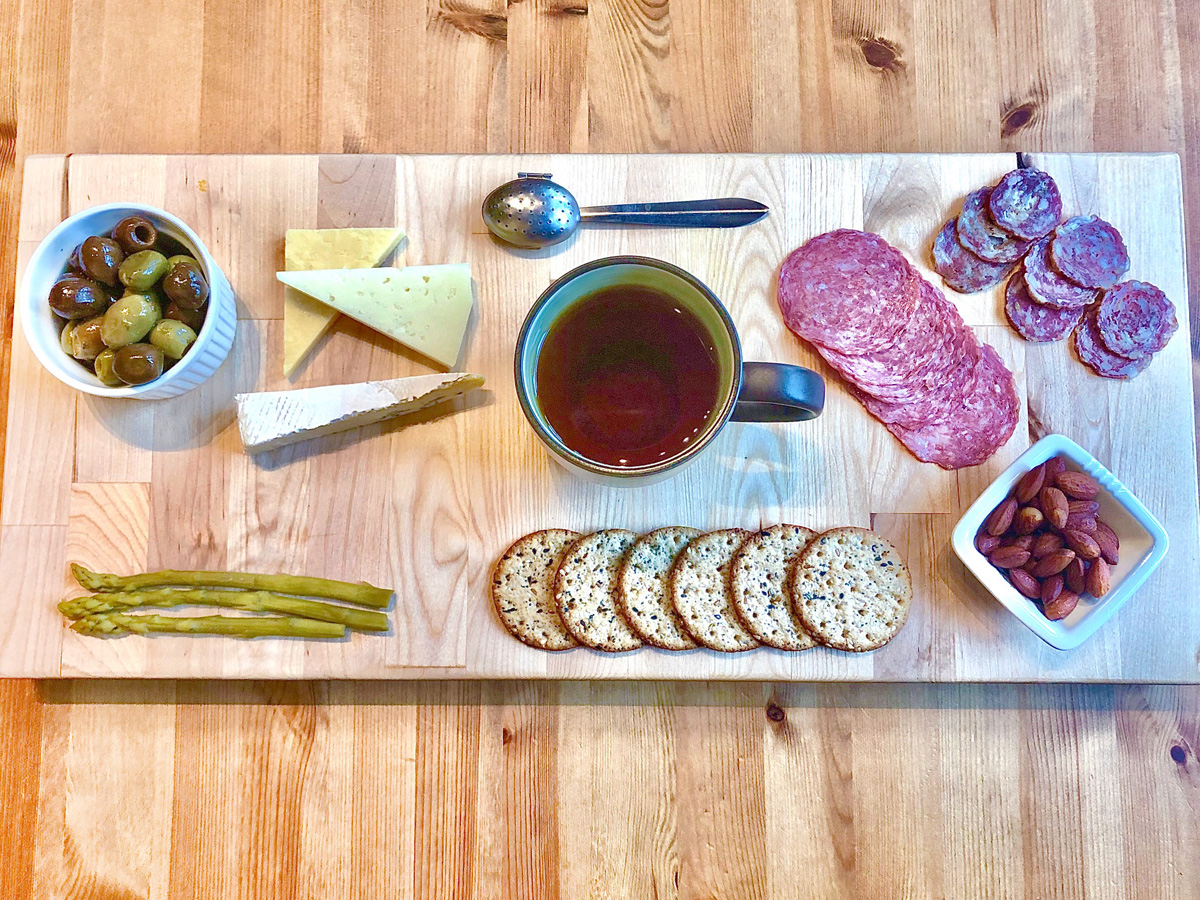 Overhead view of a wooden charcuterie board. A mug of tea sits in the center and is surrounded by cheese, meats, crackers, olives, nuts, and pickles.