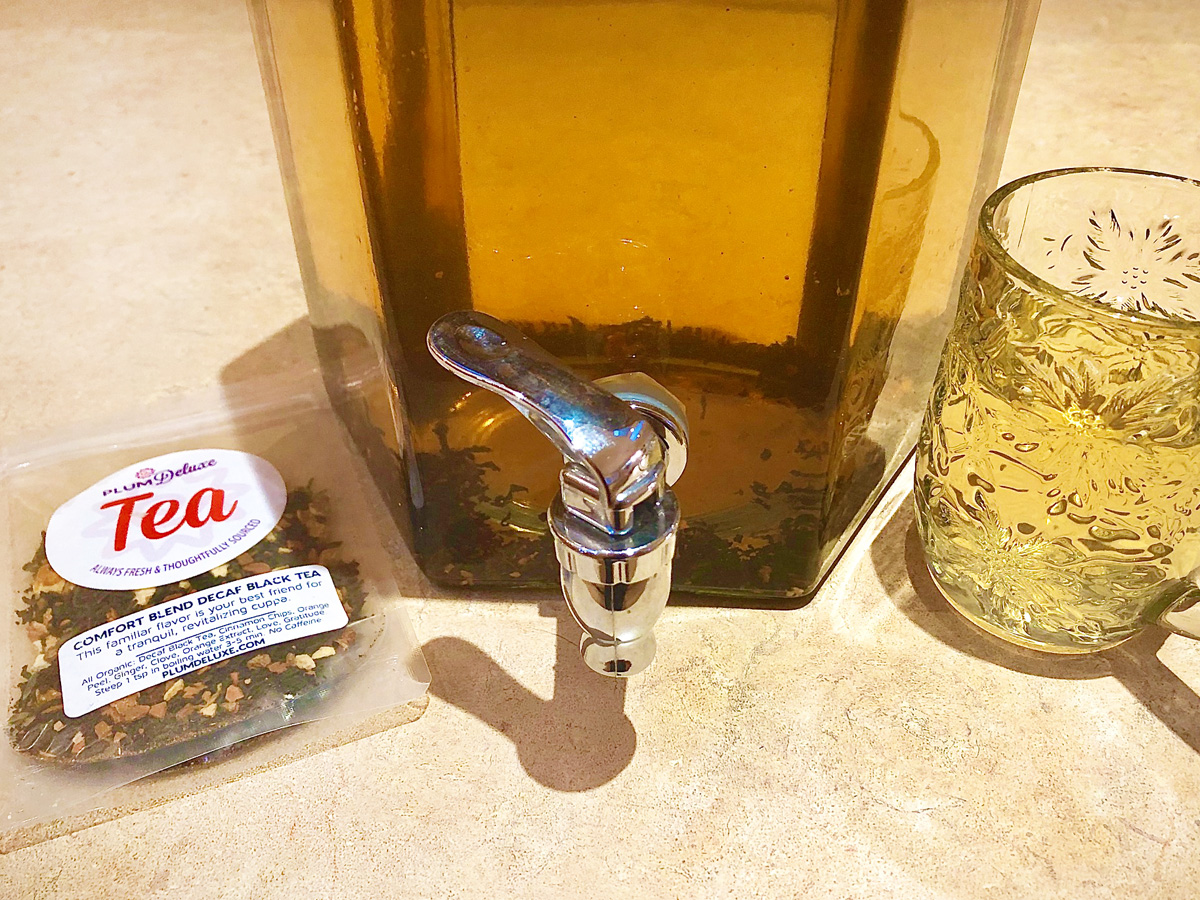 A large glass container full of sun tea sits on a counter top. A packet of Plum Deluxe loose leaf tea is on the left, while a faceted glass cup full of tea is on the right.