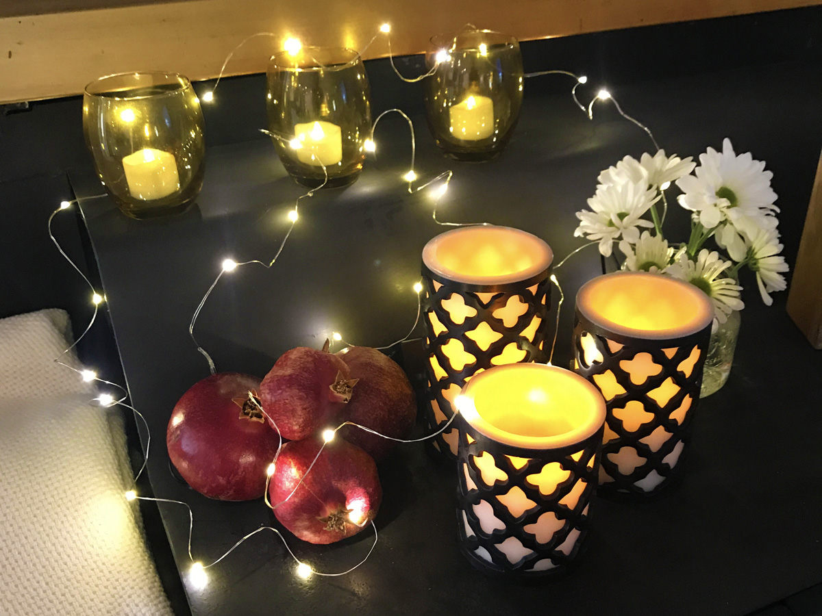 Six softly glowing candles, a string of fairy lights, four pomegranates, and a vase of white daisies are grouped together on a black table.
