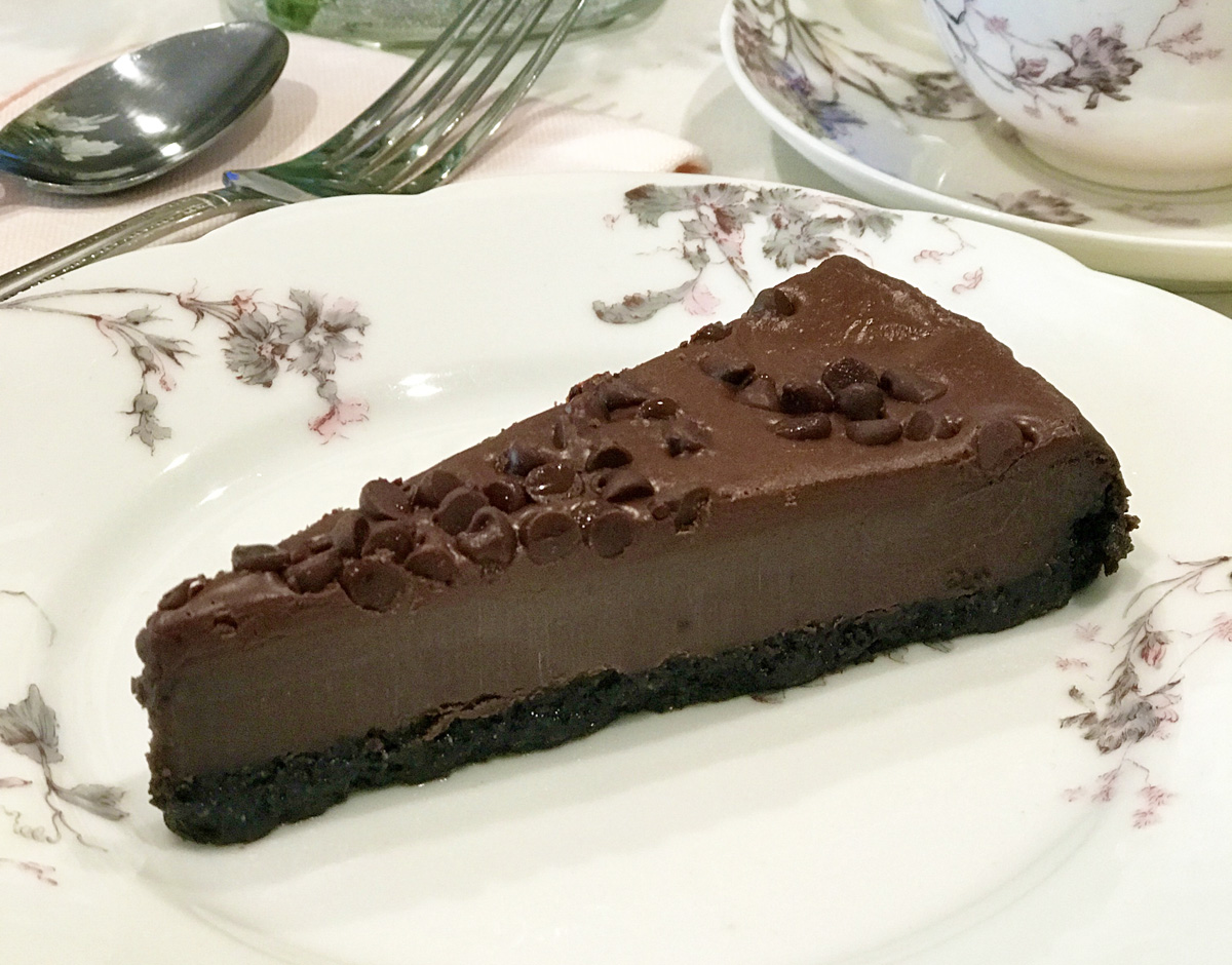 A slice of chocolate mint chip cheesecake is served on a white and purple floral plate.