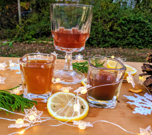 Three different green tea shots in fancy glassware sit on a wooden board with shrubbery in the background. They are surrounded by citrus slices, decorative snowflakes, evergreen boughs, pinecones, and twinkle lights.