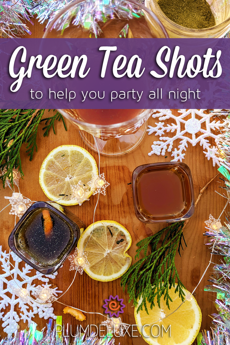 Overhead view of three green tea shots, lemon slices, evergreen boughs, decorative snowflakes, and twinkle lights on a wooden table. The overlay text reads: green tea shots to help you party all night.