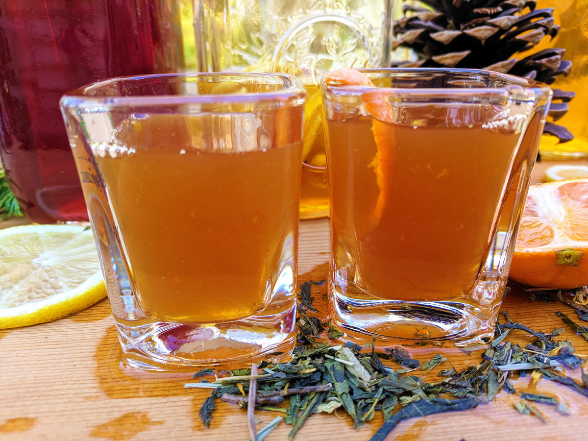Two green tea shots sit on a wooden board with citrus slices and loose leaf green tea scattered around them.