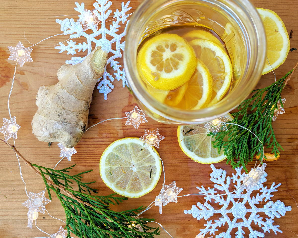 Overhead view of a jar full of honey, fresh ginger, and lemon slices on a wooden board. It is surrounded by fresh ginger root, lemon slices, evergreen boughs, decorative snowflakes, and twinkle lights.