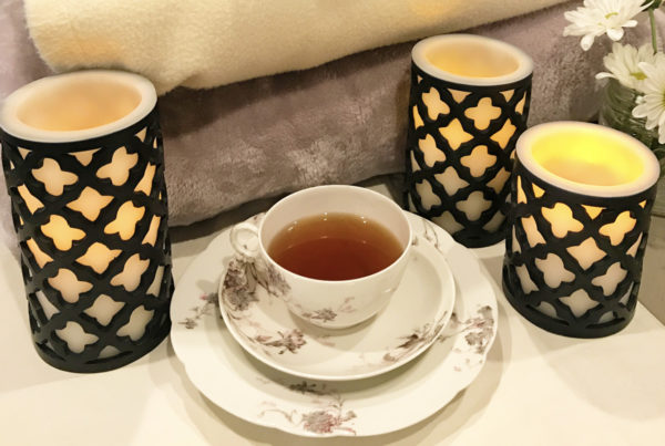 A white a floral print teacup and saucer set sits in front of three softly glowing candles and a pile of cozy blankets.