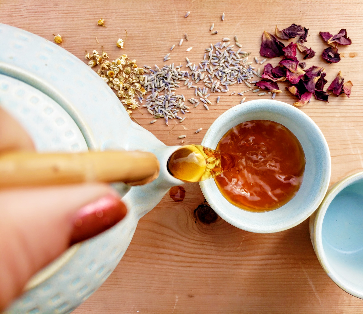Overhead view of a hand pouring a teapot of caffeine free herbal tea into a cup. Various herbs are scattered on the wooden table around it.