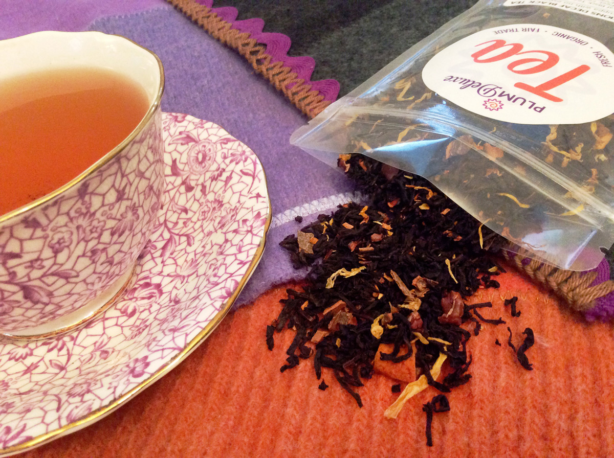 A purple and white floral teacup and an open bag of Plum Deluxe loose leaf tea sit side by side on a patchwork cloth of orange, purple, and green.