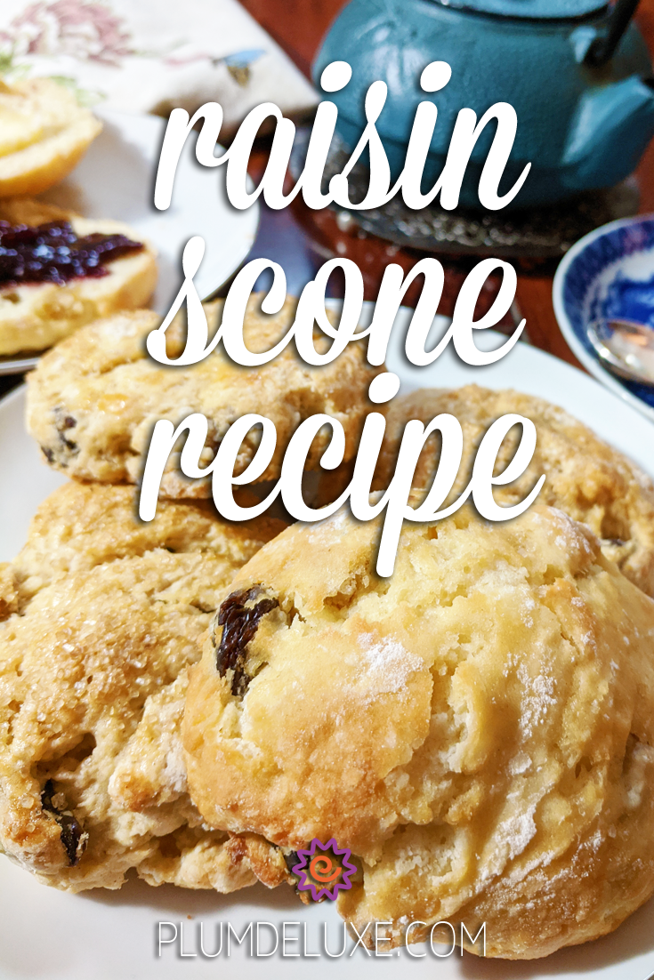Closeup of a plate full of raisin scones. A blue teapot can be seen in the background. The overlay text reads: raisin scones recipe.