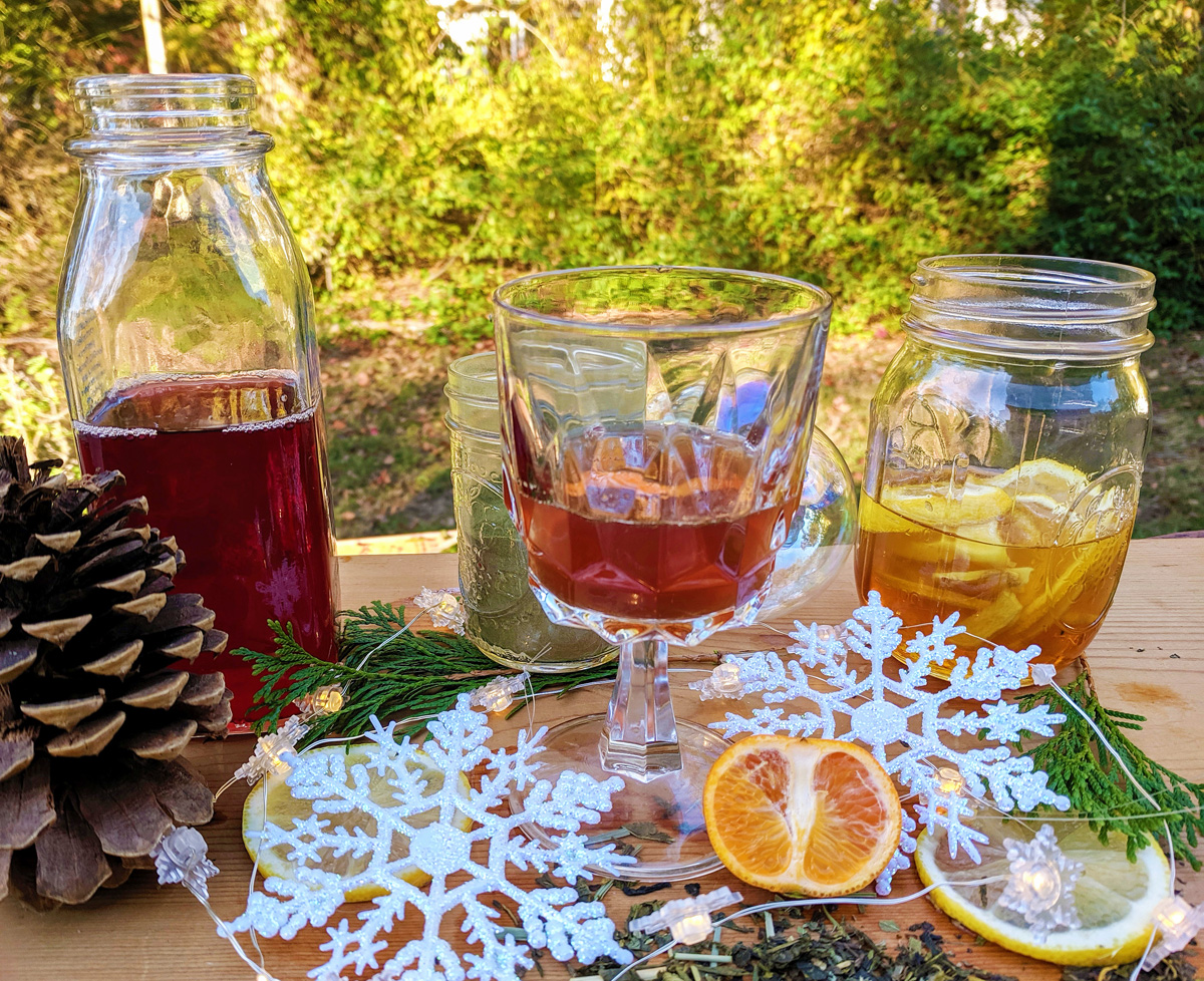A stemmed glass with a non-alcoholic green tea shot sits on a wooden board with shrubbery in the background. It is surrounded by decorative snowflakes, citrus slices, evergreen boughs, and pinecones. A jar of ginger lemon honey is on the right and a bottle of brewed tea is on the left.