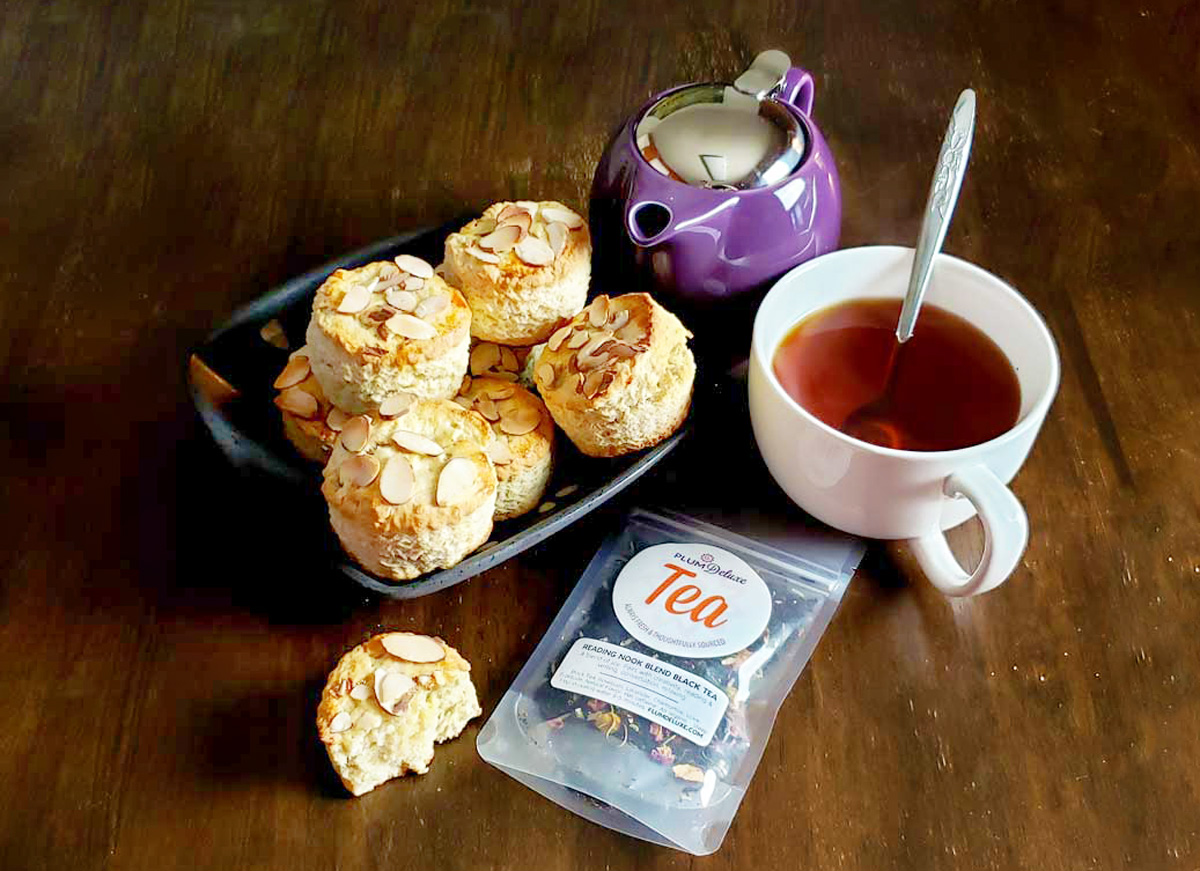 A black dish filled with almond scones sits on a dark wooden table along with a purple teapot, white teacup full of tea, and bag of loose leaf tea.