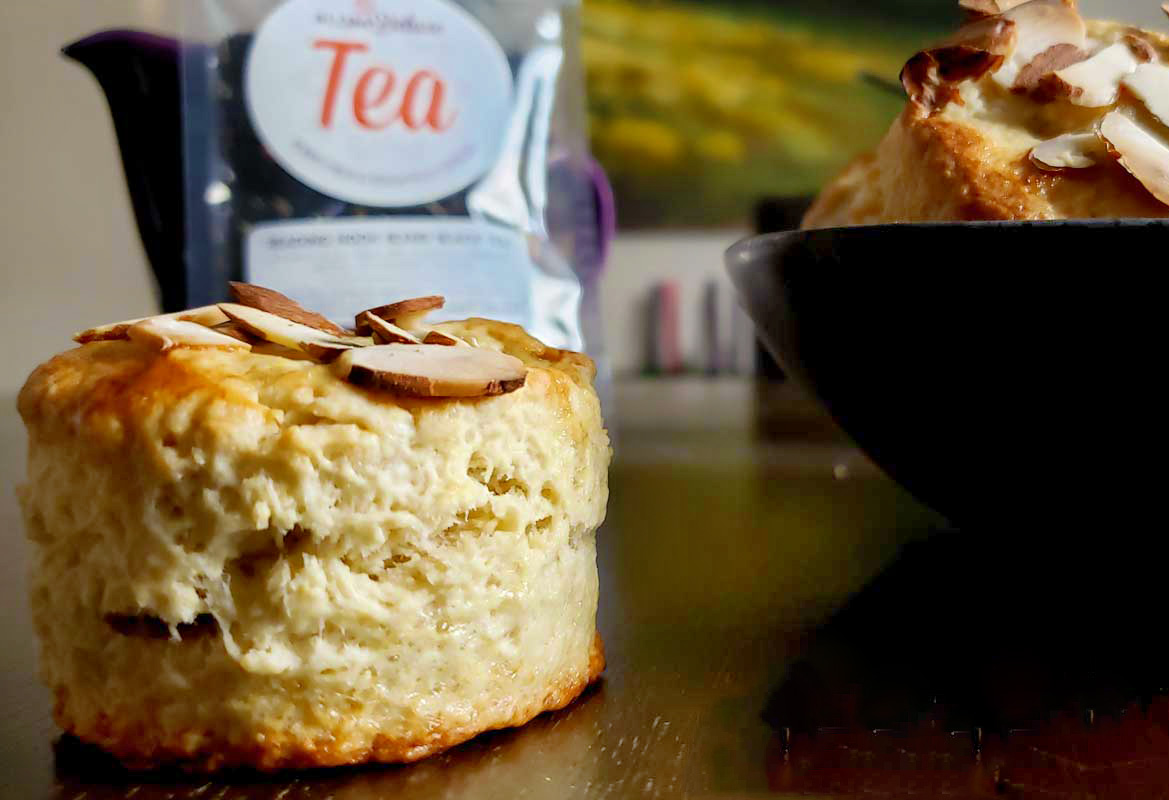 Closeup of a well-risen round scone with almond slices on top. In the background is a bag of loose leaf tea and a bowl of scones.