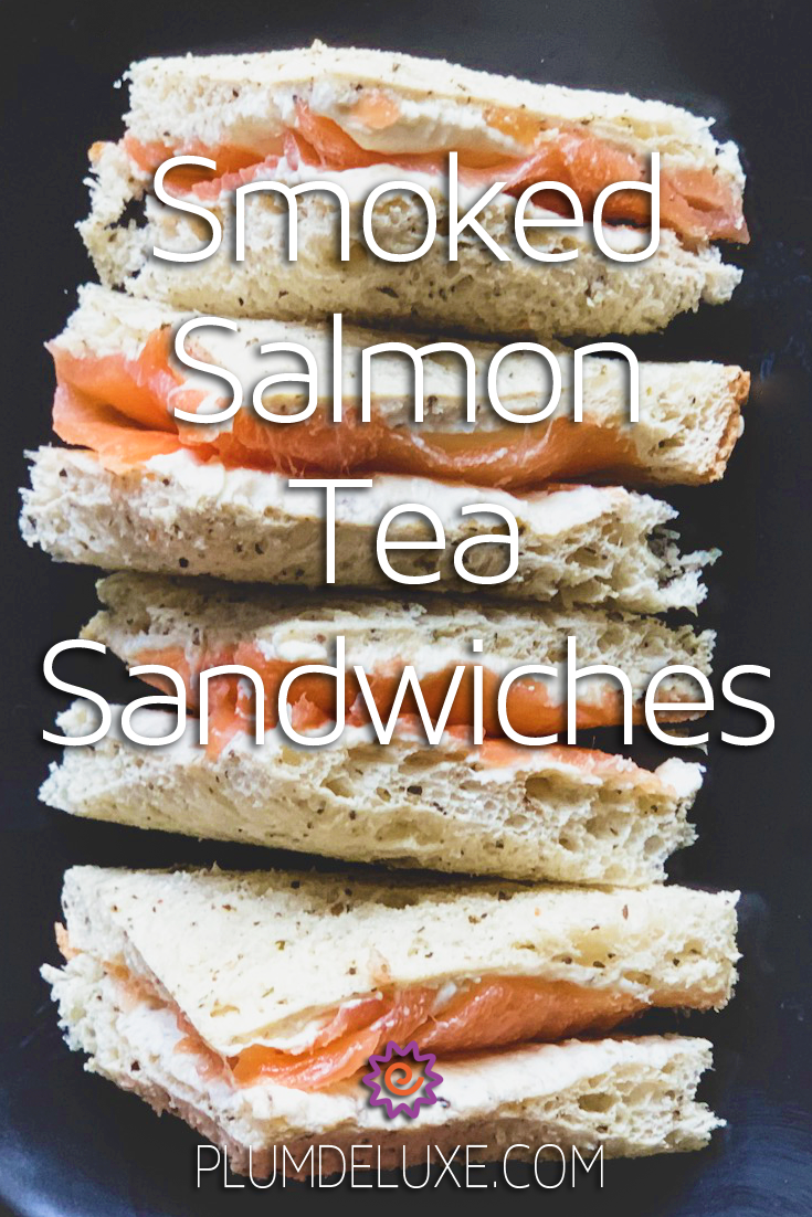 Four tea sandwiches on white bread with cream cheese and smoked salmon are stacked on a black background. The overlay text reads: smoked salmon tea sandwiches.