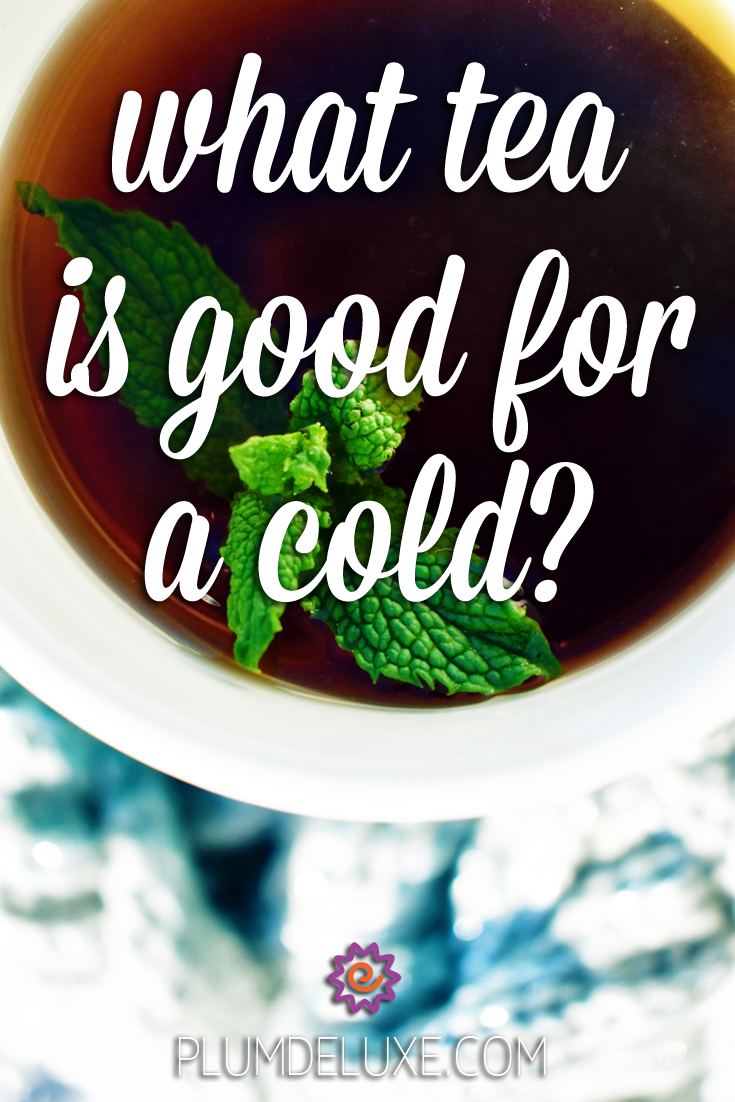 Overhead view of a white mug full of dark tea and garnished with a sprig of mint sitting on a white and blue cable knit blanket. The overlay text reads: what tea is good for a cold?