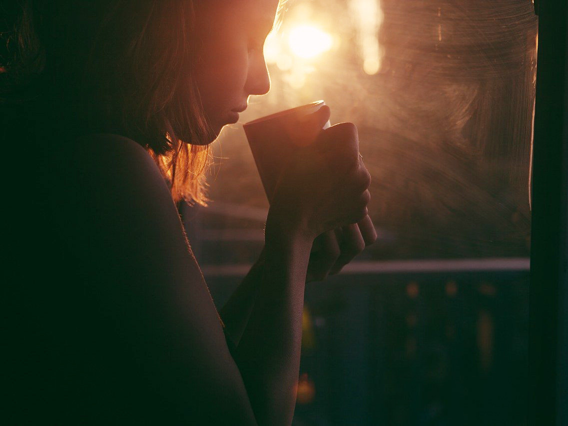 A femme person sits in front of a window and lifts a mug of tea to their lips. The room is dark, but light streams in through the window.