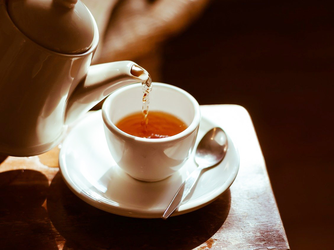 Tea is poured from a light brown tea pot into a white teacup resting on a saucer. A silver teaspoon sits on the saucer to the right of the cup.