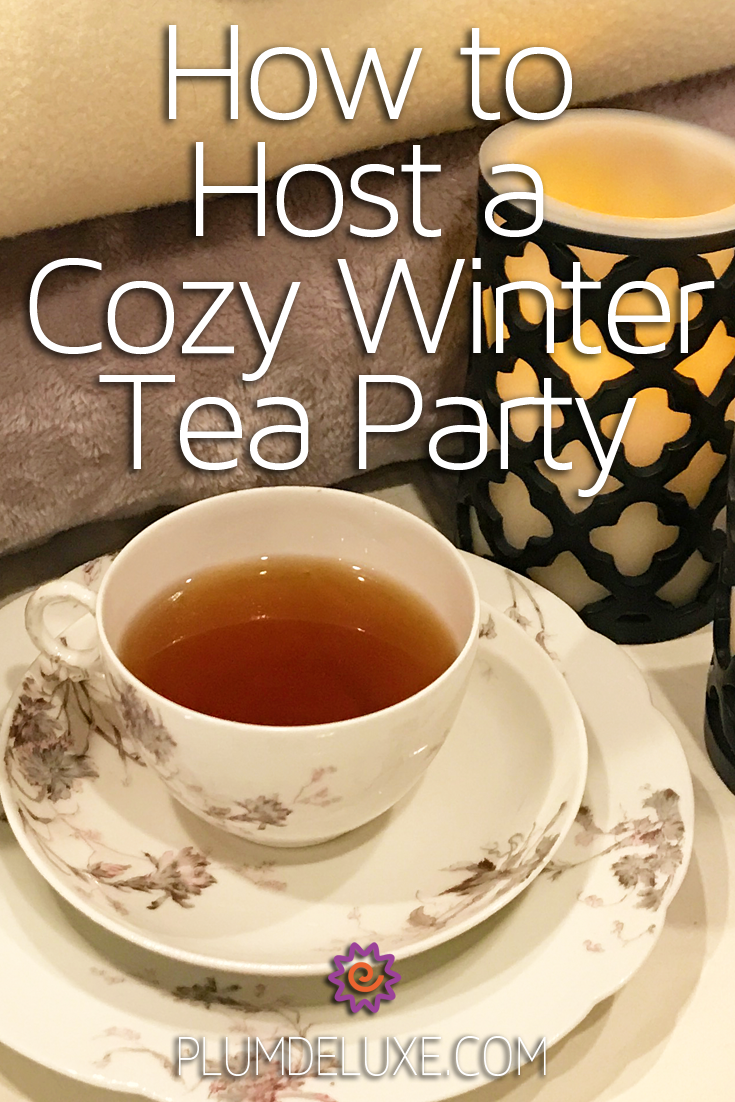 A white a floral print teacup and saucer set sits in front of a softly glowing candle and a pile of cozy blankets. The overlay text reads: how to host a cozy winter tea party.