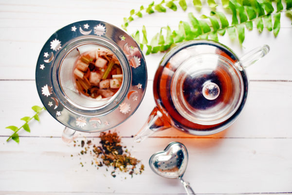Overhead view of a clear glass teapot and mug with a Celestial mesh tea nest infuser on a white wooden table. A fern leaf curls in from the top of the image.