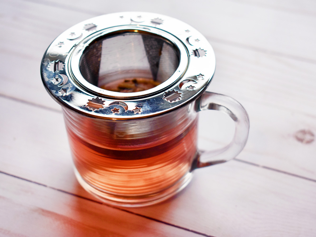 A stainless steel mesh next infuser with suns, moons, and stars on it, sitting on top of a glass teacup on a white wood table.