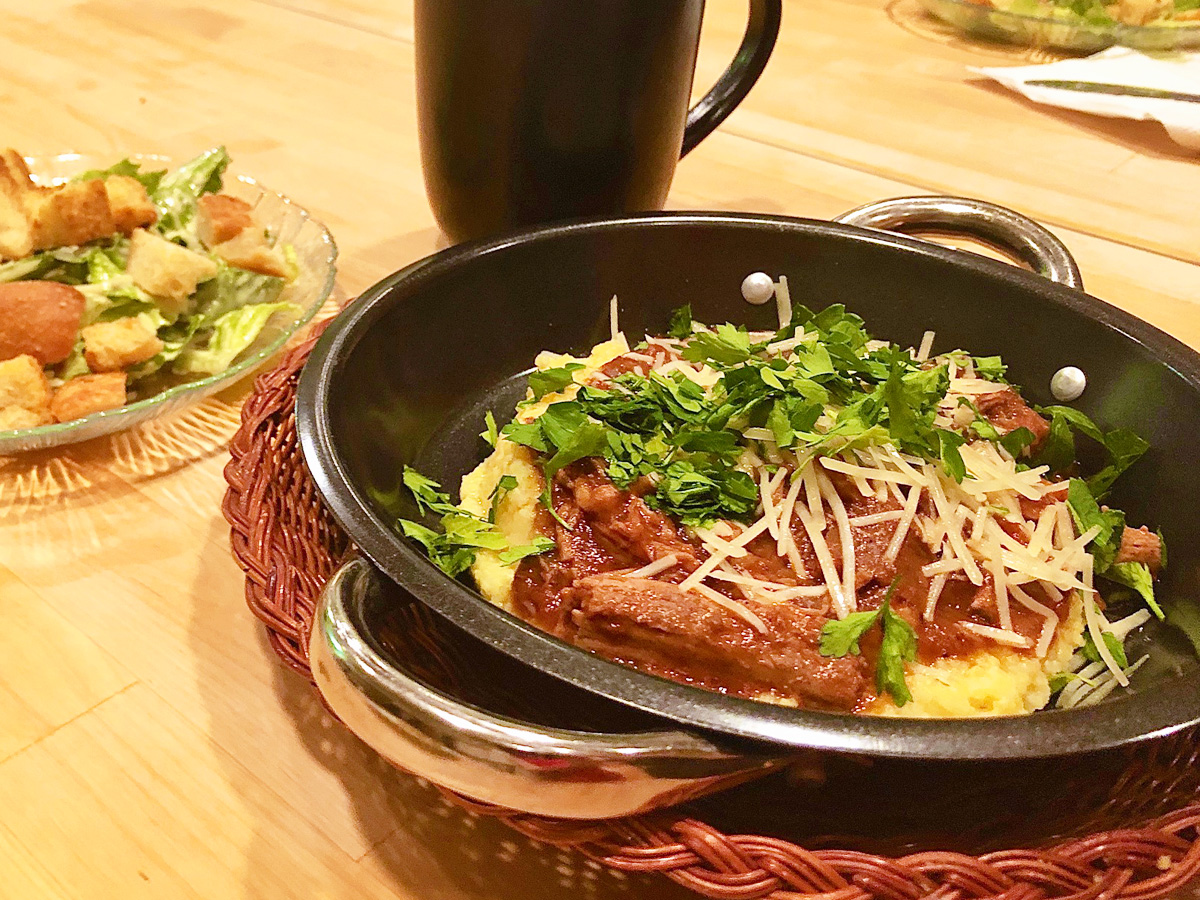 A dish of savory ribs and polenta sits on a wooden table next to a salad and a mug of tea.