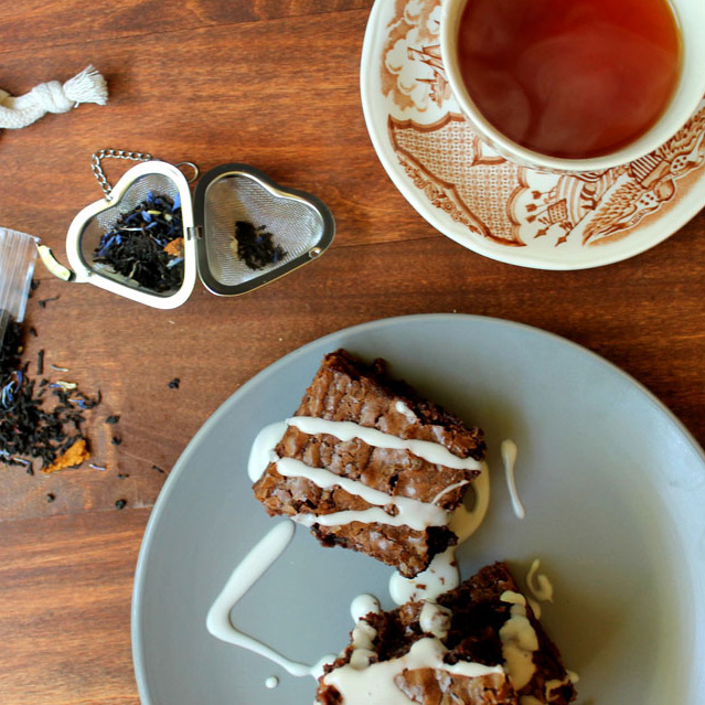 Overhead view of two earl grey brownies on a gray plate next to a brown and white teacup and saucer. They are arranged on a wooden table along with a heart shaped tea infuser full of loose leaf tea.