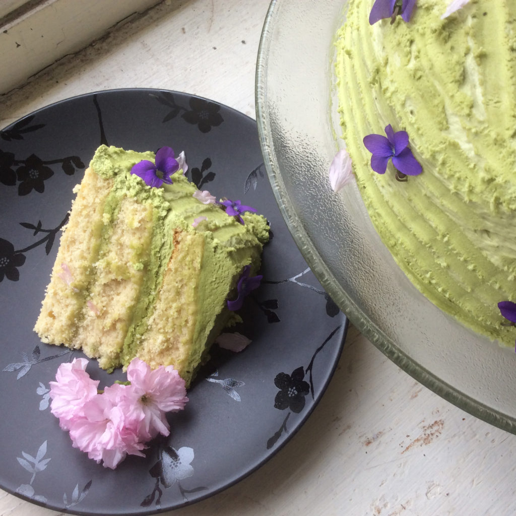 Overhead view of a slice of yellow cake with green matcha buttercream icing on a black plate garnished with a cluster of cherry blossoms. The rest of the cake can be seen peeking in from the upper corner of the frame.