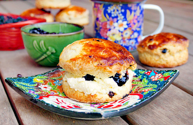 An Irish scone that has been split in half and spread with clotted cream and jam sits on a square floral plate. In the background can be seen a floral mug, more scones, and a green bowl of jam.