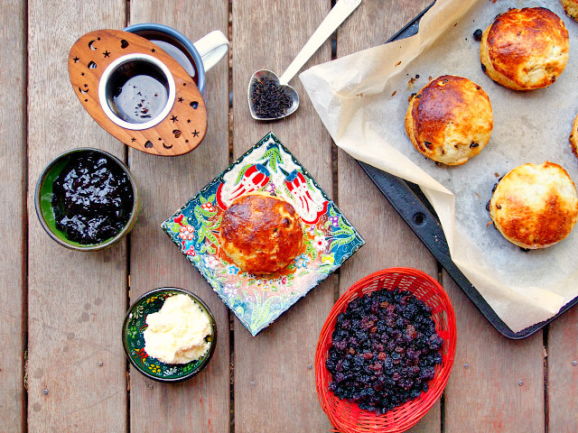 Overhead view of an Irish scone on a floral plate surrounded by black currants, butter, jam, a cup of tea, and a tray of baked scones.