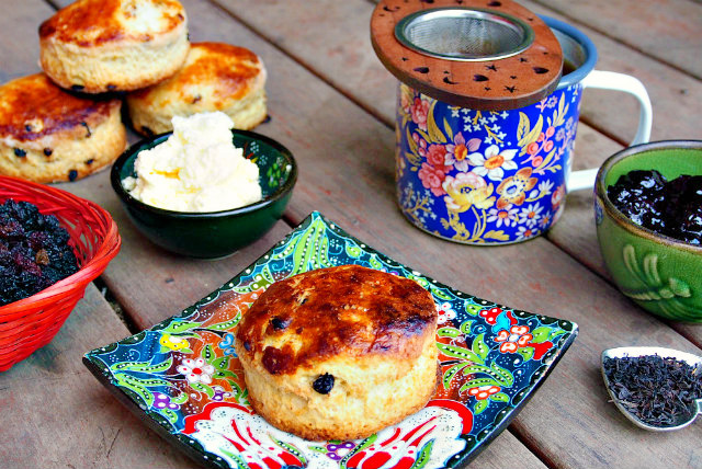 An Irish scone sits on a square floral plate surrounded by a scoop of loose tea, a green bowl of jam, a blue floral mug of tea, a bowl of clotted cream, more scones, and a basket of currants.