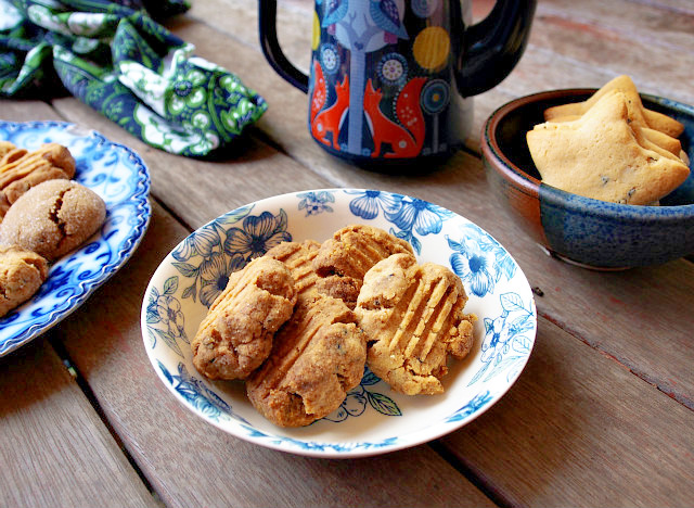 Shortbread and sugar cookies are piled in blue floral print bowls on a wooden table. A hand painted mug with foxes on it is in the background.