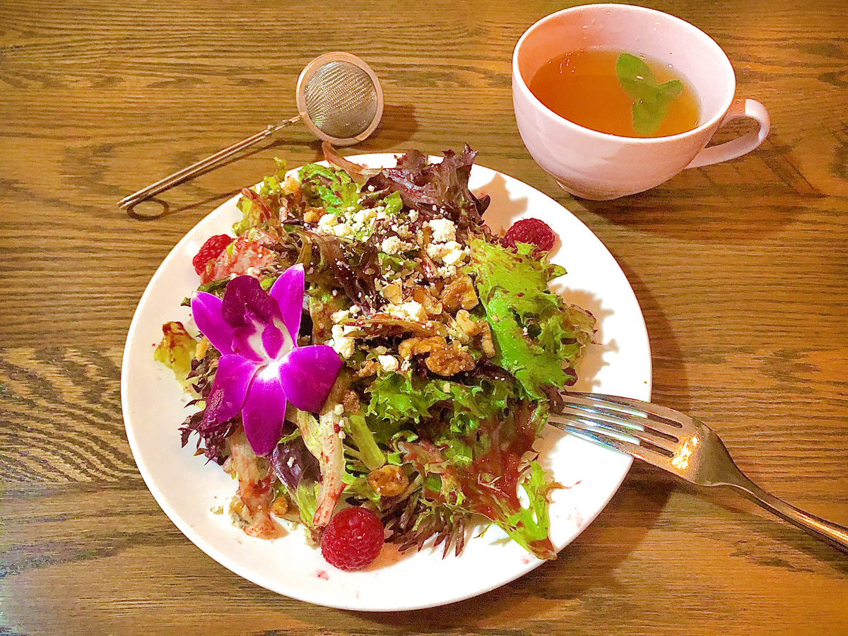 A leafy salad garnished with cheese, nuts, and an orchid sits on a wooden table next to a pink teacup full of tea and a tong-style tea infuser ball.