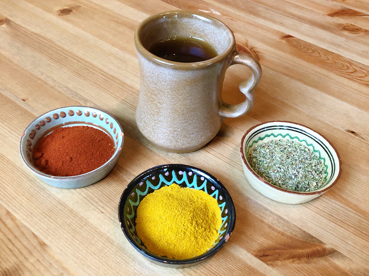 An earthenware mug full of tea sits behind three small bowls full of various spices on a wooden table.