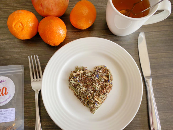 Overhead view of a white plate with a pile of loose leaf tea shaped into a heart in the center of it. To the left is a fork; to the right a knife. Above the place are three oranges, and apple, and a cup of tea.